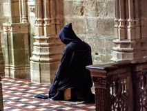 Catholic Christian Monk kneeling in humble prayer asking God for help stock photo