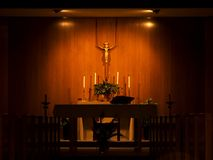 Catholic Church Alter. A picture of a Catholic church alter, with a figure of Christ on the wooden wall and candles on the alter Stock Image