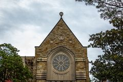 A Catholic Church with a Beautiful Circular Window. This is a one hundred year old Catholic church with wonderful stone work and a gorgeous circular window royalty free stock image