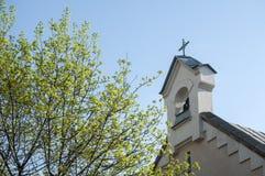 Catholic Church and blossomed tree Stock Photos