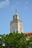 Catholic church with clock. Catholic church on the island in France on blue sky background stock image
