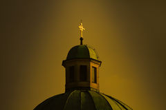 Catholic church with cross in golden glow Stock Photos