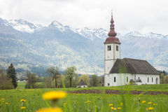 Catholic church in field among Alps Stock Photo