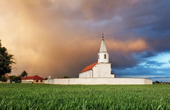 Catholic church in field on sunset Royalty Free Stock Photos