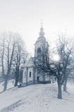 Catholic church hill. Slovenia, Skofja Loka. Catholic church on hill in snow and fog. Slovenia, Skofja Loka area, St. Andrej Church. Monochromic image Royalty Free Stock Images