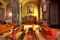 Catholic church interior. Line of pews and confessional as part of catholic church interior in Serralunga D'Alba, Northern Italy Royalty Free Stock Photos