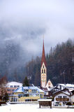Catholic church in Langenfeld. View to Längenfeld`s church and houses with low clouds covering forest at background Royalty Free Stock Image