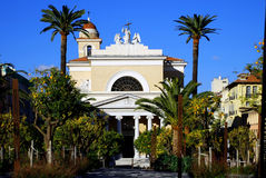 Catholic church in Nice, France. Small pink Catholic church among palm trees and tangerine trees on a clear sunny day Stock Images