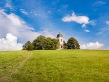Catholic church on top of hill in bright light. Christian church or chapel with white tower on top of the hill in the forest, horizon between green ground and Stock Image