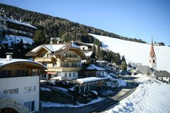 Catholic church and village in the Italian dolomites in wintertime with snow. royalty free stock photos