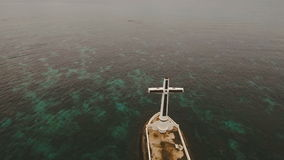 Catholic cross in the sea. Aerial view Sunken Cemetery cross in Camiguin Island, Philippines. Large crucafix marking the underwater sunken cemetary of the coast stock video footage