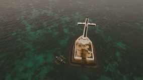 Catholic cross in the sea. Aerial view Sunken Cemetery cross in Camiguin Island, Philippines. Large crucafix marking the underwater sunken cemetary of the coast stock video