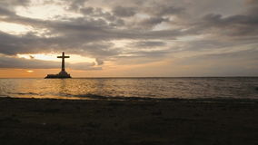 Catholic cross in the sea. Aerial view Sunken Cemetery cross in Camiguin Island, Philippines,sunset. Large crucafix marking the underwater sunken cemetary of stock footage