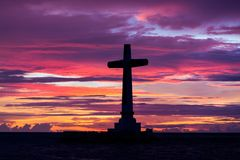 Catholic cross silhouette. In the sunken cemetery at dusk, Camiguin island, Philippines Royalty Free Stock Photos