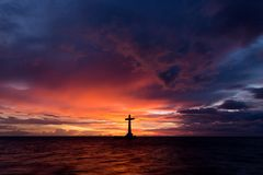 Catholic cross silhouette. In a sunken cemetery at dusk, Camiguin island, Philippines Stock Photography