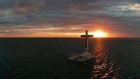 Sunken Cemetery cross in Camiguin island, Philippines. Catholic cross in sunken cemetery in the sea at sunset, aerial drone. colorful sky during the sunset stock video