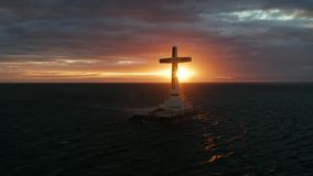 Sunken cemetery cross in Camiguin island, Philippines. Catholic cross in sunken cemetery in the sea at sunset, aerial drone. colorful sky during the sunset stock footage