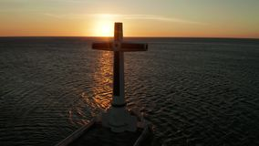 Sunken Cemetery cross in Camiguin island, Philippines. Catholic cross in sunken cemetery in the sea at sunset, aerial drone. Large crucafix marking the stock footage