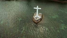 Sunken Cemetery cross in Camiguin island, Philippines. Catholic cross in sunken cemetery in the sea at sunset, aerial drone. Large crucafix marking the stock video footage