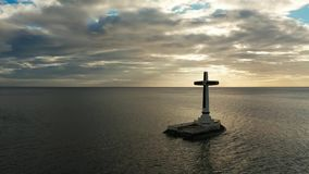 Sunken cemetery cross in Camiguin island, Philippines. Catholic cross in sunken cemetery in the sea at sunset, aerial drone. Large crucafix marking the stock video