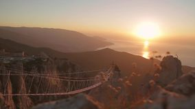 Catholic Cross at Sunset. View of the catholic cross and rope ladder over the abyss. Crimea, Ukraine.Ayu Dag Mountain view from the top of Ai Petri mountain stock video footage