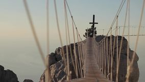 Catholic Cross at Sunset. View of the catholic cross and rope ladder over the abyss. Crimea, Ukraine.Ayu Dag Mountain view from the top of Ai Petri mountain stock footage