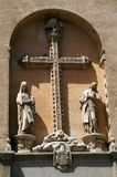 The Catholic cross and two figures in the arch on the wall of the building. Stone bird on the top of the cross. Ornament on the cross. Christianity. Religion Stock Image