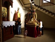 Catholic devotees pray to religious images inside a prayer room at the Antipolo Cathedral. Stock Photo