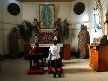 Catholic devotees pray to religious images inside a prayer room at the Antipolo Cathedral. Stock Image