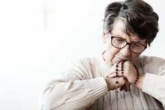 Catholic grandmother in melancholy praying to god with red rosary with cross stock photo