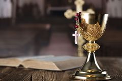 Catholic holidays – Easter. Place for typography and logo. Holy communion. Catholic theme. The Cross, chalice, rosary and Bible  Rustic wooden background Royalty Free Stock Photos