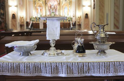 Catholic liturgical object. Chalice, communion wafers, wine, wat. Catholic liturgical objects displayed over table at church. Chalice, communion wafers, wine Royalty Free Stock Photo