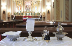 Catholic liturgical object. Chalice, communion wafers, wine, wat. Catholic liturgical objects displayed over table at church. Chalice, communion wafers, wine Stock Photo
