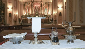 Catholic liturgical object. Chalice, communion wafers, wine, wat. Catholic liturgical objects displayed over table at church. Chalice, communion wafers, wine Royalty Free Stock Image