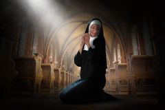 Nun Praying, Prayer, Christian Religion, Catholic. A Catholic nun is praying in church. The Christian religion woman prays for peace, hope, love, God, Jesus, and stock photos