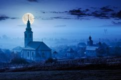 Catholic and orthodox churches at foggy night. In full moon light. lovely countryside scenery in autumn royalty free stock photos