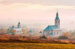 Catholic and orthodox churches at foggy sunrise. Lovely countryside scenery in autumn. creative toning royalty free stock photo