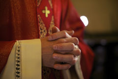 Catholic priest on altar praying during mass. Catholic priest on altar praying with hands joined during mass service in church Royalty Free Stock Image