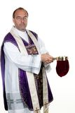 Catholic priest collects. A Catholic priest at the gathering in front of a white background royalty free stock image