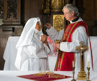 Communion and nun. Catholic priest giving holy communion to a nun Royalty Free Stock Photos