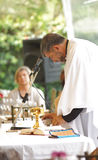 Catholic priest giving Mass outdoors in the garden of a house Royalty Free Stock Photo