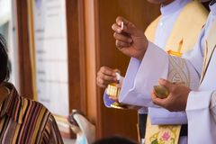 Catholic priest granting the Communion in Thailand stock image
