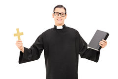 Catholic priest holding holy bible and a golden cross. Isolated on white background Stock Photos