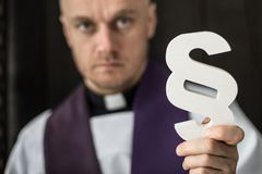 Catholic priest holding wooden paragraph. The symbol of law. Law and religion stock images