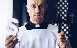 Catholic priest holding wooden paragraph. The symbol of law. Law and religion stock photography