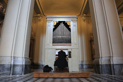 Catholic priest playing the pipe organ Royalty Free Stock Image