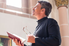 Catholic priest reading bible in church stock image