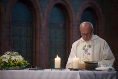 Catholic priest reads holy bible Stock Photo