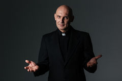 Catholic priest standing and doing welcome gesture Royalty Free Stock Photos