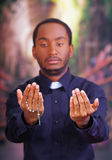 Catholic priest wearing traditional clerical collar shirt standing facing camera, holding hands out with rosary cross. Looking forward, religion concept Royalty Free Stock Image